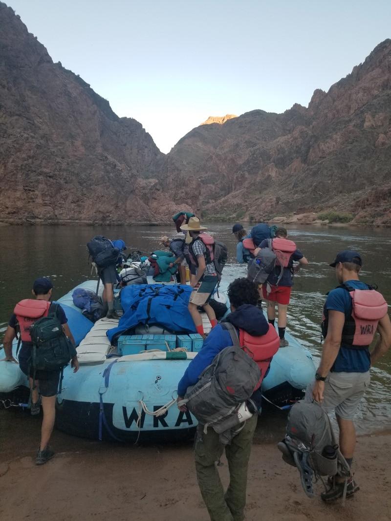 Young Men Climbing into Raft